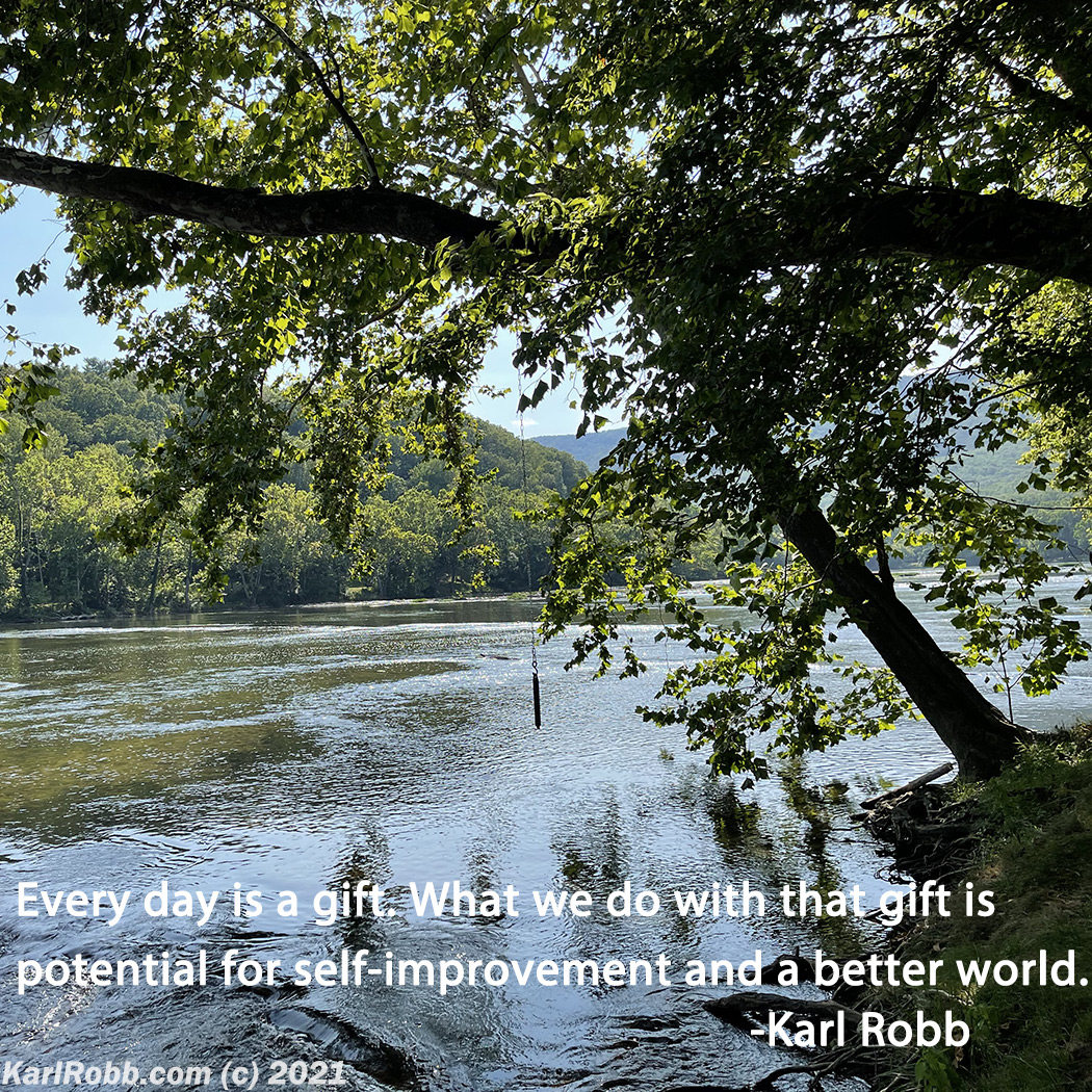 Photo by Karl Robb of river with green trees on the banks and mountains in the background with the words Every day is a gift. What we do with that gift is potential for self-improvement and a better world.